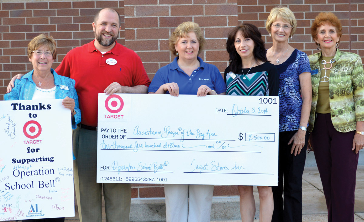 Kirk Kveton, store manager of the Target store at Baybrook Mall, holds up the check surrounded by Assistance League members, from left, Philanthropic Vice President Sarah Foulds, Operation School Bell Chairman Cindy-Senger Lewis, Altimus, Priscilla Magnussen and President-Elect Peggy Clause.