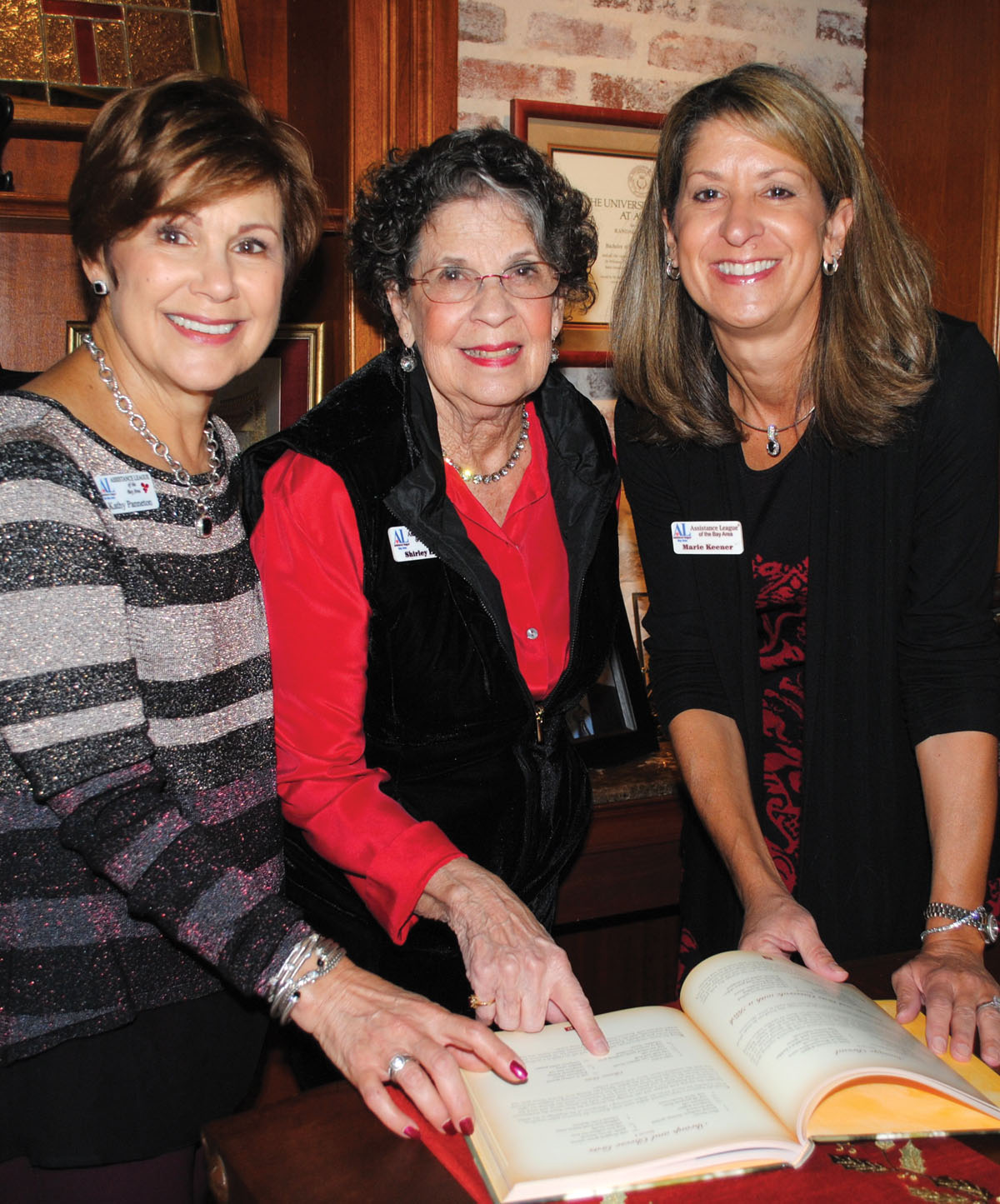 Assistance League members Kathy Panneton, Shirley Lang and Marie Keener, from left, look for a recipe in the League cookbook during Holiday Open House.