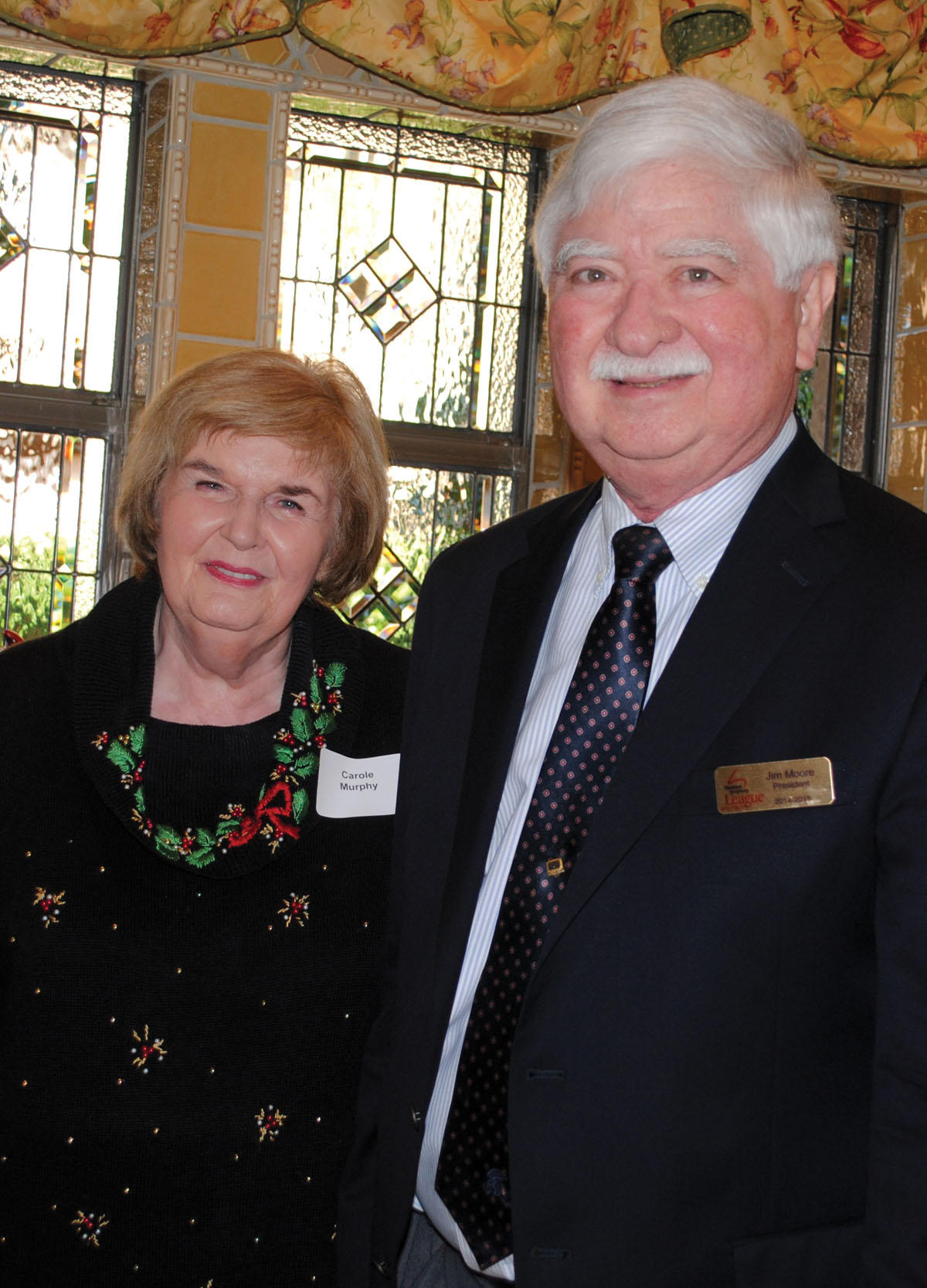 Hostess Carole Murphy and Houston Symphony League Bay Area President Jim Moore prepare to welcome the crowd to the group's Holiday Brunch at the Murphy home in Brook Forest.
