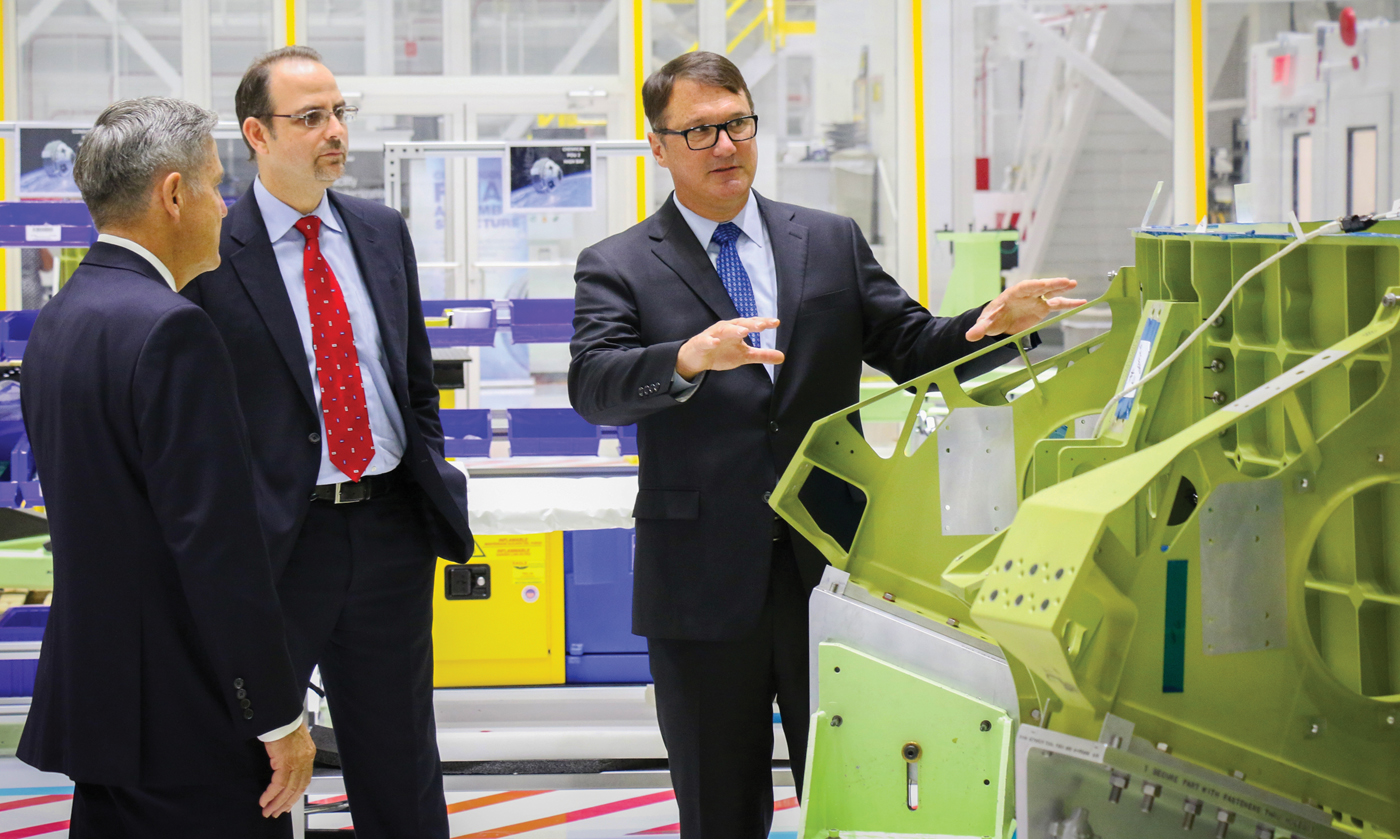 Boeing Vice President – Commercial Programs John Mulholland shows CST-100 Starliner flight hardware to Kennedy Space Center Director Robert Cabana, left, and Bastion Technologies President Jorge Hernandez.