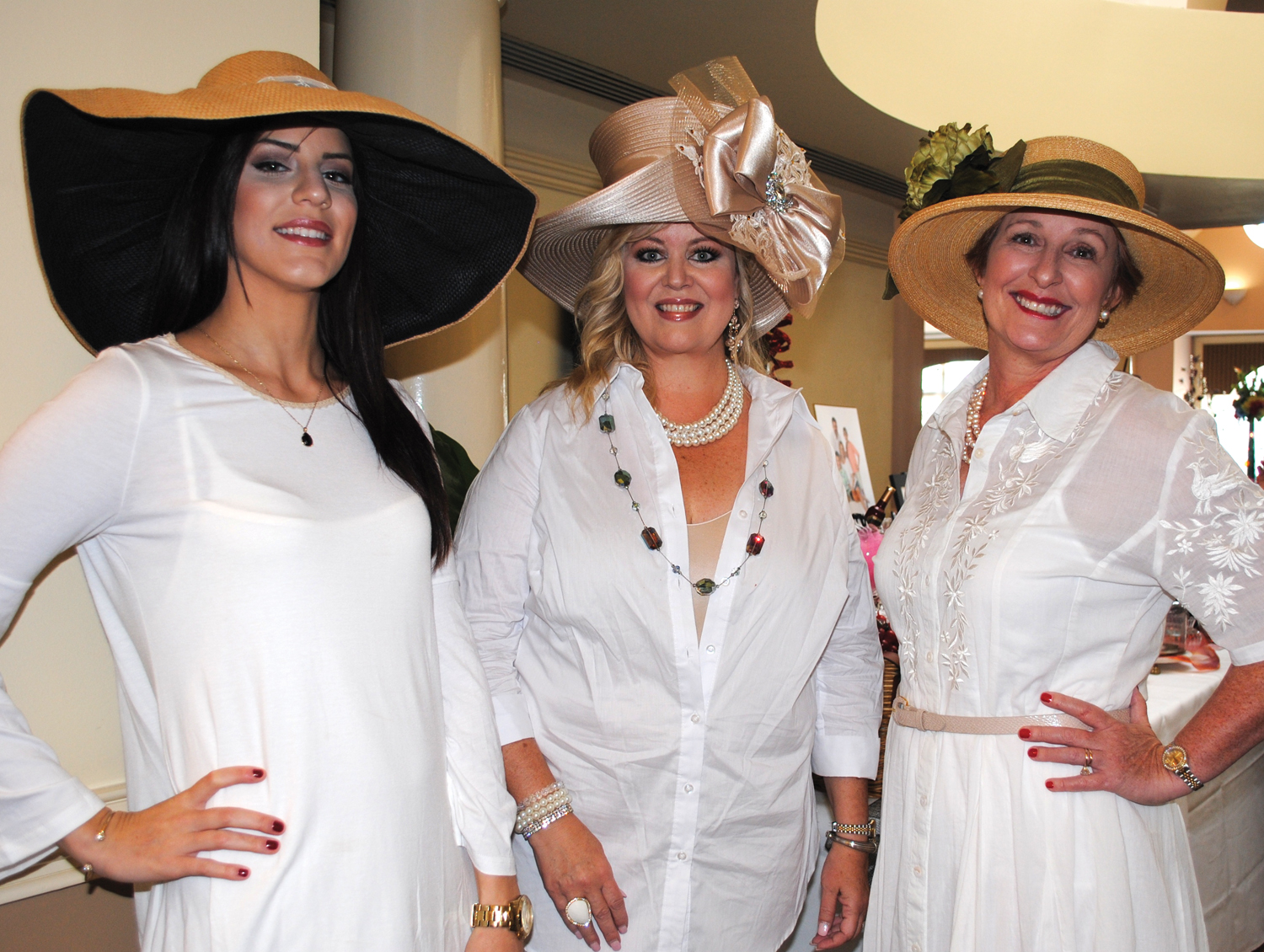 Alexandra Stanley, Jana Miller and Missy Rohrer, from left, show off their hats as they walk about the ballroom during the Just A Pretty Table Luncheon.