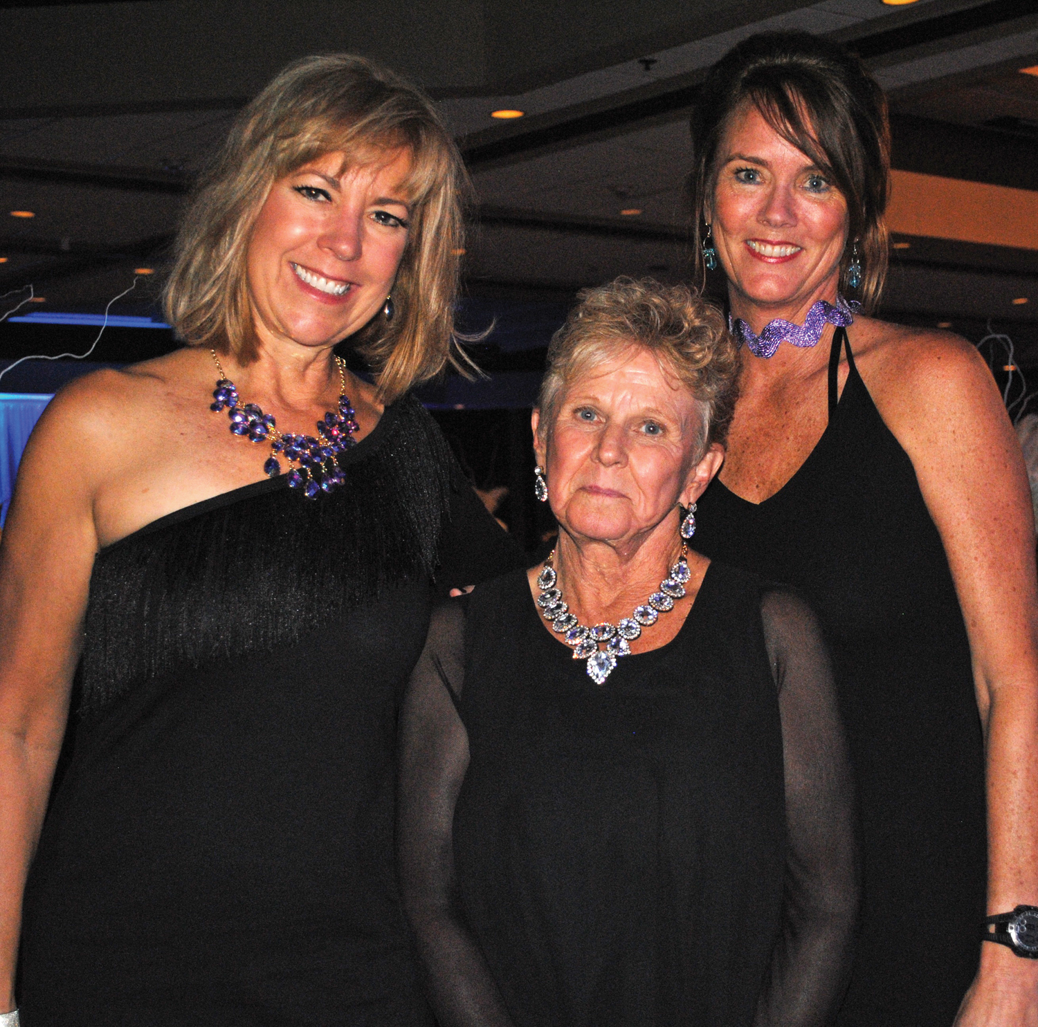 BATP Co-Founder Pam Merrill, center, receives congratulations on being a Cornerstone Honoree at the Purple and Teal Ball by emcee Carla Medlenka, left, and Ball Chairman Lisa Dishman.