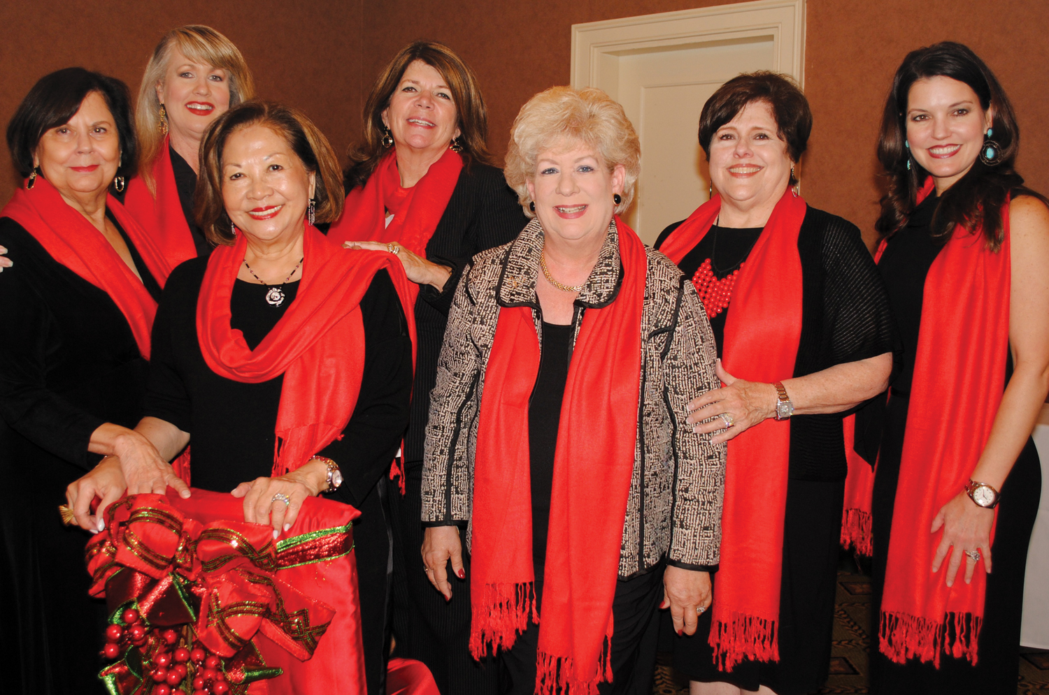 These ladies added quite a splash of color to the Just A Pretty Table Luncheon with their Christmas theme. They are, from left, Donna Rieves, Doreen Stringer, Connie Lopez, Kippy Caraway, Cassandra Brunson, Ann Wismer Landolt and Tonya Ferris.