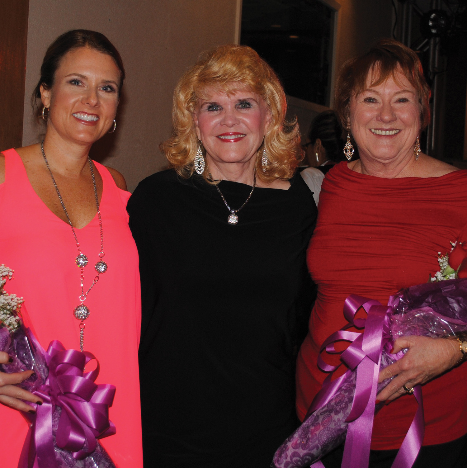Clear Lake Area Panhellenic President Kay Lee Benoit, center, presents bouquets of roses to Chairman Ellen King, left, and Co-Chairman Karen Weber to thank them for all their hard work putting the fall fashion show luncheon together.