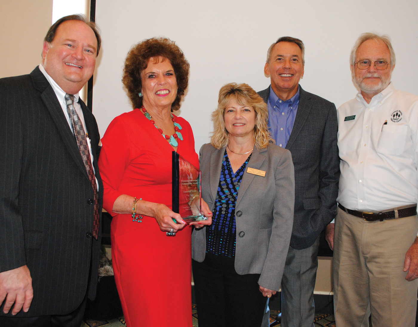 Emmeline Dodd holds the Conservation Award she was presented by the Armand Bayou Nature Center Board of Directors at a luncheon at Bay Oaks Country Club. With her are, from left, BAHEP executive and emcee Dan Seal, ABNC Board of Directors President Linda Retherford, Trendmaker Homes President Will Holder and ABNC Executive Director Tom Kartrude.