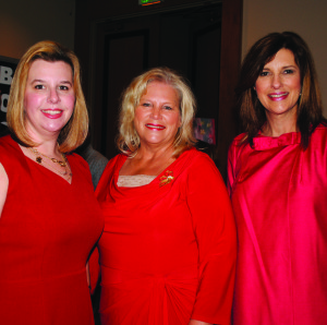 Memorial Hermann Southeast staff members Ashlea Quinonez, left, and Rebecca Lilley, right, welcome Fay Picard, who came to the Go Red for Women Luncheon to represent State Rep. Greg Bonnen, who was tied up in Austin with legislative duties.