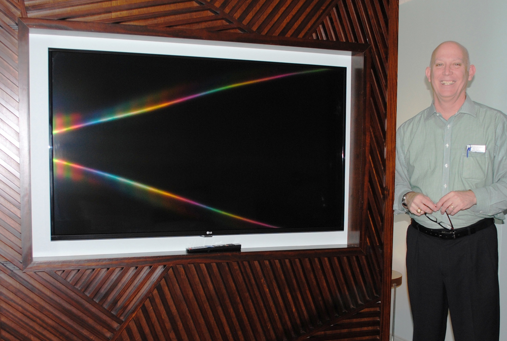 General Manager Roy Green shows off new 55-inch TV.