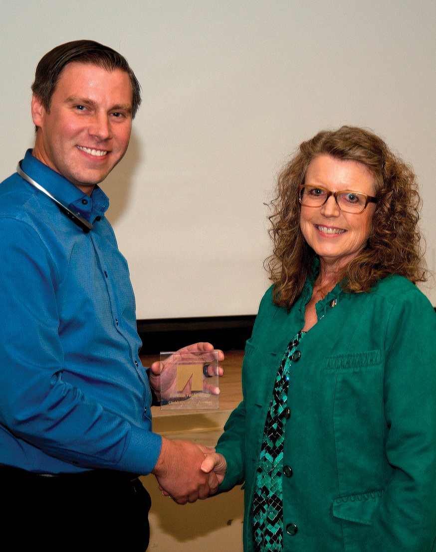 Barrios Technology's Ben Matson, is presented the company's Annual Gold BEAR Award for the development and implementation of a specialized packing assessment SharePoint tool. by Barrios President and CEO Sandy Johnson.