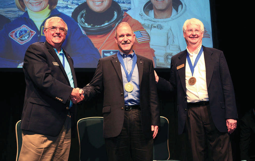 NASA Associate Administrator for and astronaut John Grunsfeld, center, is inducted into the U.S. Astronaut Hall of Fame at Kennedy Space Center in Florida. Shaking his hand is Dan Brandenstein, chairman of the board of directors for the Astronaut Scholarship Foundation, as former NASA astronaut Steve Hawley looks on.