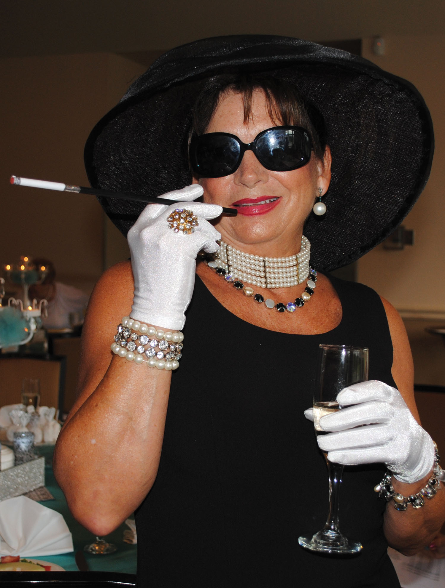 "Well, dahling, come and join us, Kathleen Courville says while offering a welcoming smile to Assistance League members arriving for ""Breakfast at Tiffany's"" at Bay Oaks Country Club."