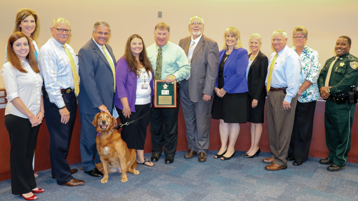 Sheriff Henry Trochesset, center, holds Aldo's retirement plaque as he joins CCISD trustees and Superintendent Dr. Greg Smith for a picture of the transfer of the drug detection dog to a therapy dog working for the school district.