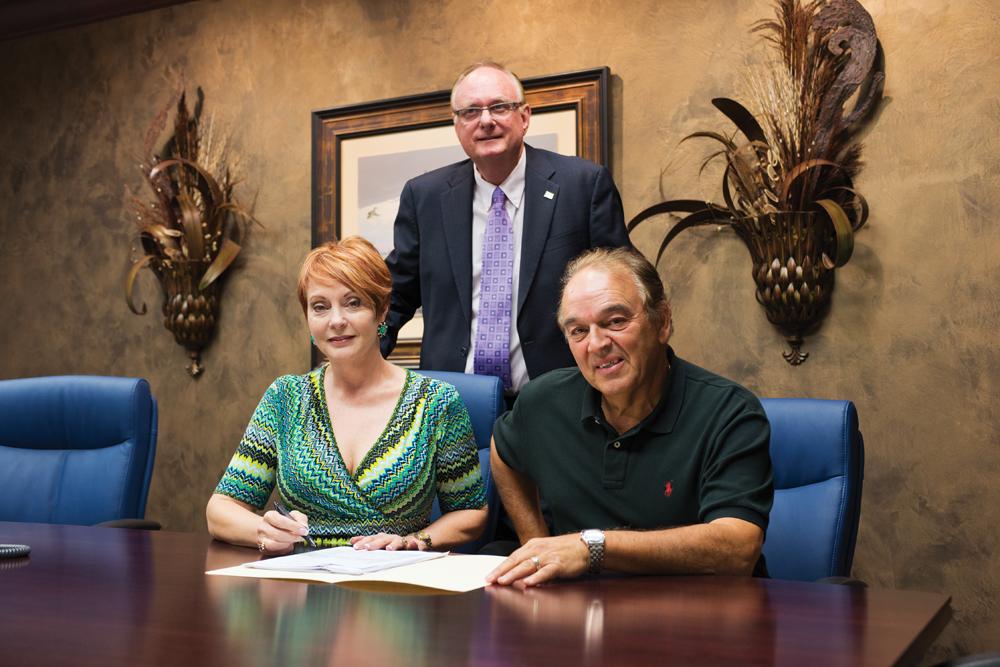Leslee Farley, Allegiance VP/Lender, left, Yanni Demartinos, co-owner of Stellar Financial and Frank Law, bank office president, standing.