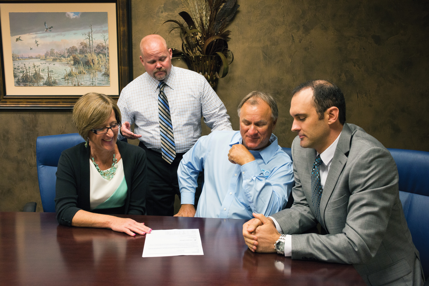 VP/Office Manager Libby McGee, left, VP/Lender Jay Farley, standing, and VP James Waguespack, right, consult with Mike Carlton, owner of Triple C Electric.