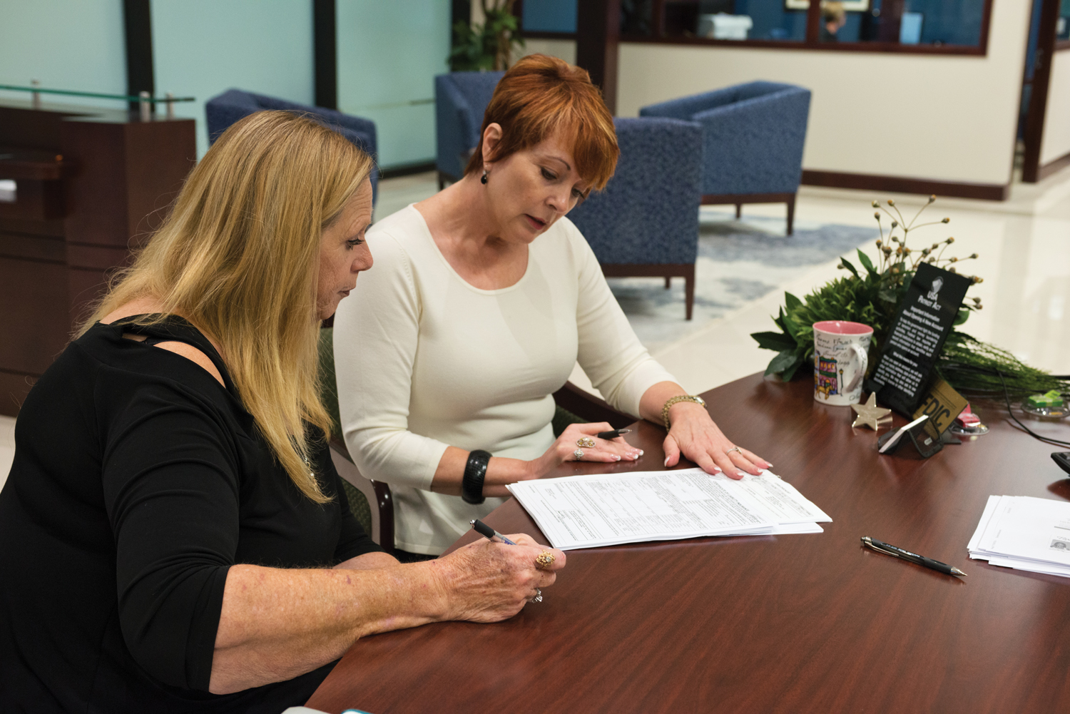 Owner of Clear Creek Equipment Rental, Sally Williams, one of the first Allegiance Bank customers, updates some documents with VP Leslee Farley.