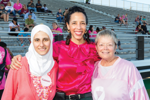 From left, MD Anderson physicians Sausan Abouharb and Valerie Reed joined with Ann Hammond, Clear Creek ISD board president and breast cancer survivor, to address the crowd with a message about breast cancer awareness during Clear Creek High School's football game against Brazoswood on Oct. 9.